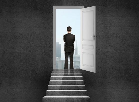 man looking through open door